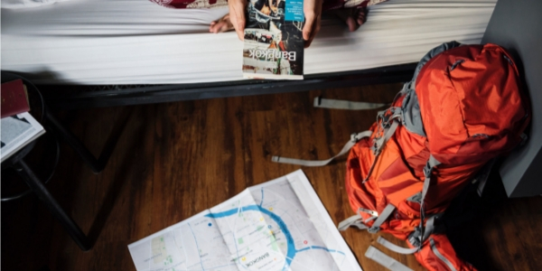 Woman Holding Bangkok Travel Guide with Map and Backpack